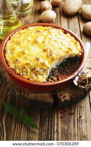 Potato casserole with meat and nettle on the  table - stock photo