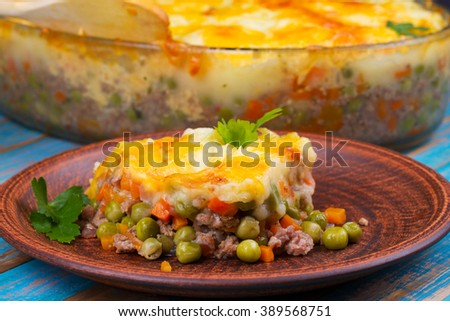 Potato, cheese, meat, carrot, onion and green peas casserole on blue ...