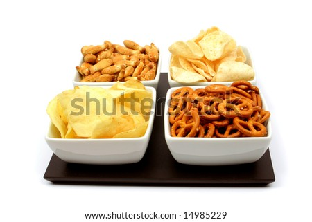 Potato chips and other salty snacks in square bowls isolated on white - stock photo