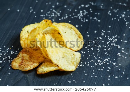 Potato chips and sprinkled salt on a dark wooden background, selective focus - stock photo
