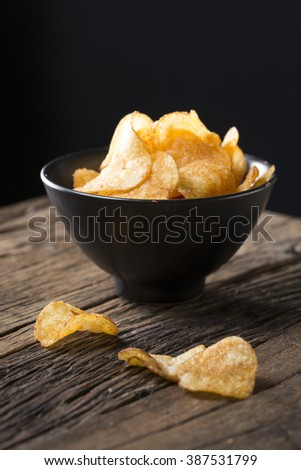 Potato chips in a bowl. A heap of potato crisps piled up in a bowl. The food is sitting on a rustic wooden background.  - stock photo