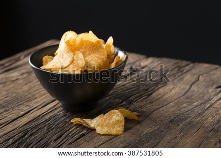 Potato chips in a bowl. A heap of potato crisps piled up in a bowl. The food is sitting on a rustic wooden background.