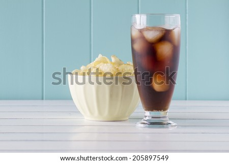 Potato chips in a bowl and a glass of cola on a white wooden table with a robin egg blue background. Vintage Style. - stock photo