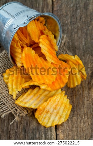 potato chips in a bucket on wooden surface - stock photo