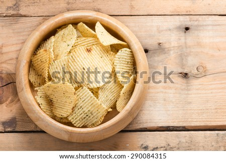 Potato chips in a wooden bowls on wood background. - stock photo