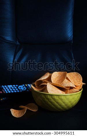 potato chips in bowl on sofa at night - stock photo