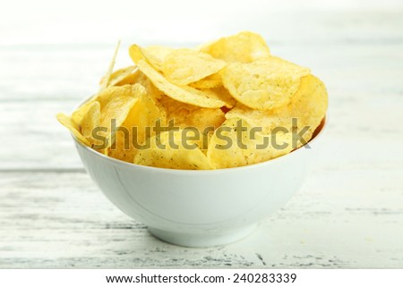 Potato chips in bowl on white wooden background - stock photo
