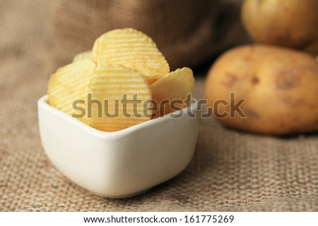 Potato chips in ceramic bowl on a sack background. - stock photo