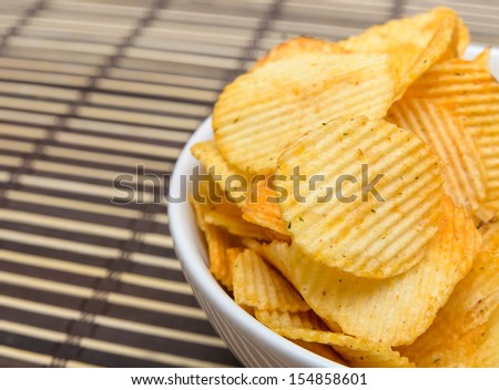 Potato chips in white bowl on bamboo mat