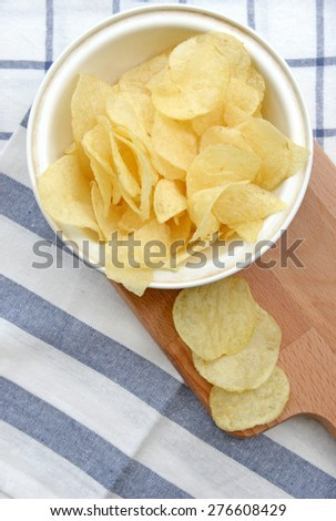 potato chips in wooden plate - stock photo
