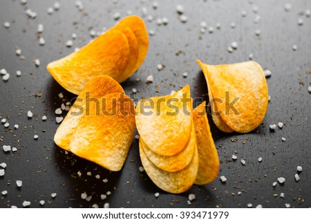 potato chips on a dark background - stock photo