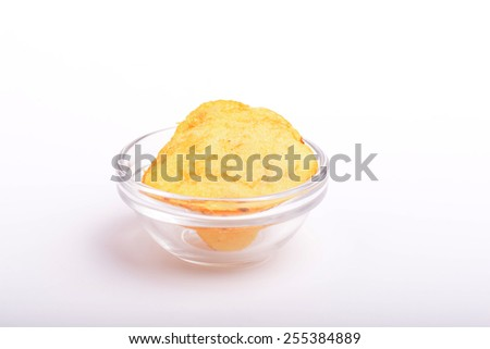 Potato chips on glass plate, close up - stock photo