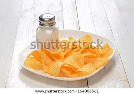 Potato chips on the plate with salt shaker on wooden table - stock photo