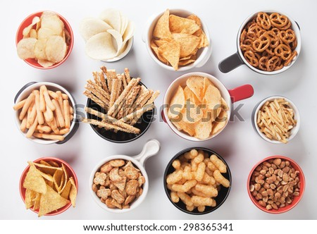 Potato chips,pretzels, roasted peanuts and other salty snacks over white background - stock photo