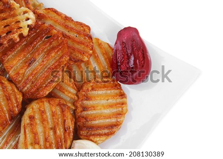 potato chips served with small pickled eggplants on small white plate isolated on white background - stock photo