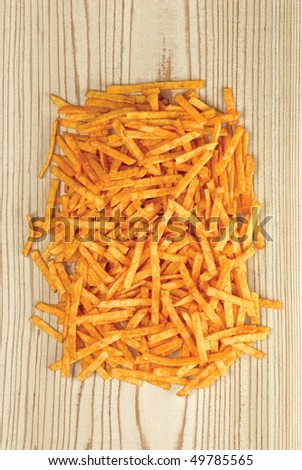 Potato chips with ketchup flavor, on wooden background - stock photo