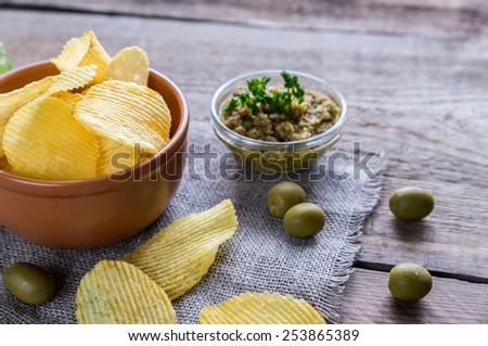 Potato chips with olive tapenade - stock photo