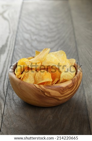 potato chips with paprika, on wood oak table - stock photo