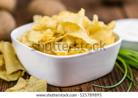 Potato Chips with Sour Cream taste as high detailed close-up shot on a vintage wooden table (selective focus)