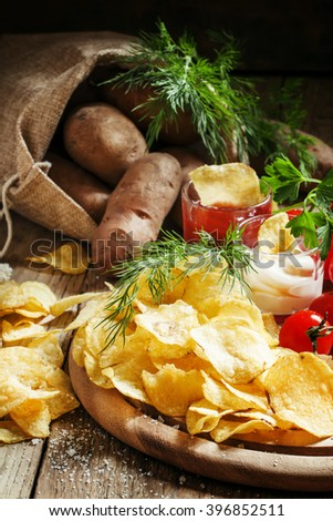 Potato chips with tomato and cheese sauce, dill and salt, selective focus - stock photo