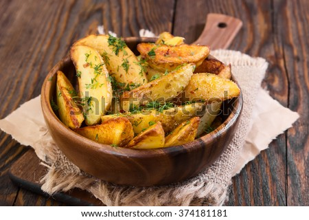 Potato country style with dill in wooden bowl on wooden background - stock photo