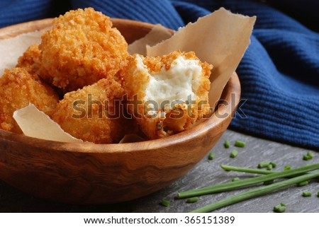 Potato croquettes in wooden bowl with fresh chives on slate cutting board. Closeup with selective focus on opened croquette. - stock photo