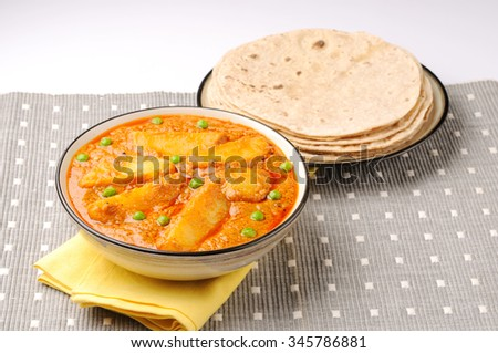 potato curry or aalu masala or aaloo masala with green peas, served with indian bread