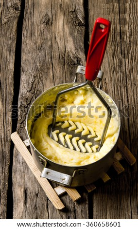 Potato food . Cooking mashed potatoes with pestle on wooden background. - stock photo