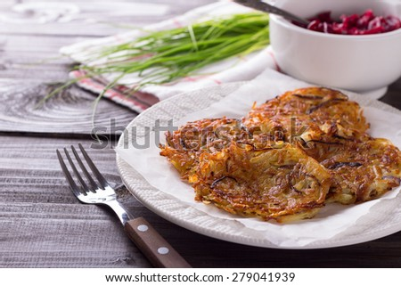 Potato fritters with red onion and spices, beet salad, a bunch of green onions on a wooden surface - stock photo