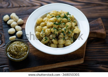 Potato gnocchi served with basil pesto in a glass plate