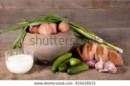 potato in a pot, cucumbers, bread, milk on a wooden background