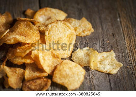 Potato kettle chips/crisps scattered on a textured wooden background. Copy space around - stock photo