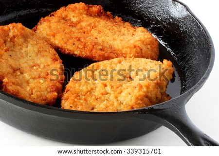 Potato latkes frying in cast iron skillet  - stock photo