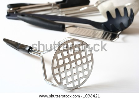 Potato masher and other kitchen utensils in the background. - stock photo