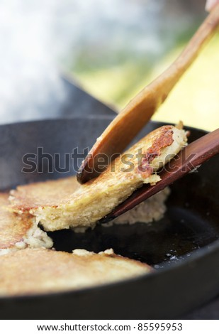potato pancakes frying in pan with wooden paddles outdoors
