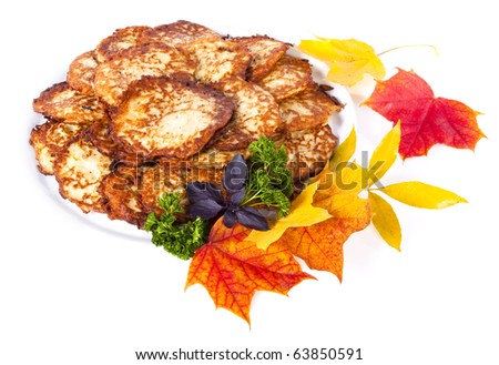 Potato pancakes in a dish decorated with maple leaves - stock photo