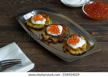 Potato pancakes(latkes) with yogurt and red caviar - stock photo