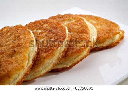 Potato pancakes served on white plate with sour cream