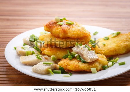 potato pancakes with herring and onion on a plate - stock photo