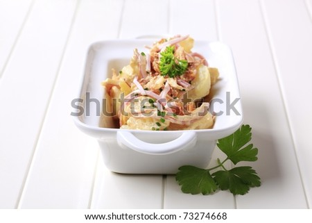 Potato salad sprinkled with ham and cracklings - stock photo