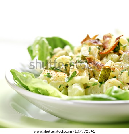 Potato salad with bacon on a green plate - stock photo