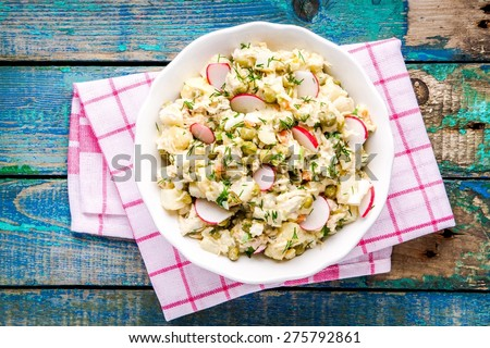 potato salad with fresh radishes in a white bowl on a rustic wooden table - stock photo