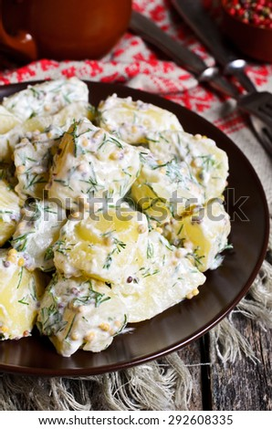 Potato salad with mustard seeds and white filling in rustic style - stock photo