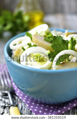 Potato salad with salted herring,marinated onion and eggs in a blue bowl on rustic background.