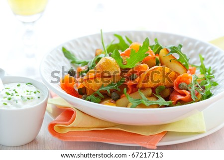Potato salad with smoked salmon,capers,rocket and sauce - stock photo