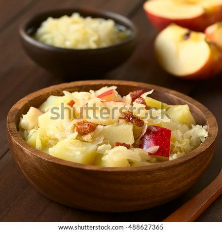 Potato, sauerkraut and apple salad with fried bacon served in wooden bowl, photographed with natural light (Selective Focus, Focus in the middle of the salad)