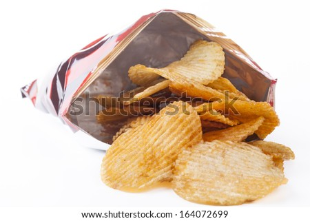 Potato ships pouring out of bag isolated on white background - stock photo