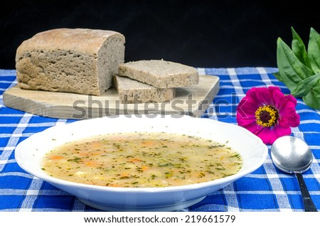 Potato soup with homemade bread and flower - stock photo