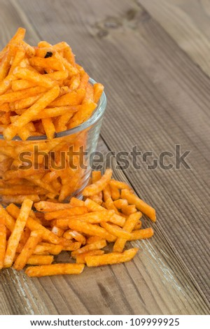 Potato Sticks in a glass on wooden background