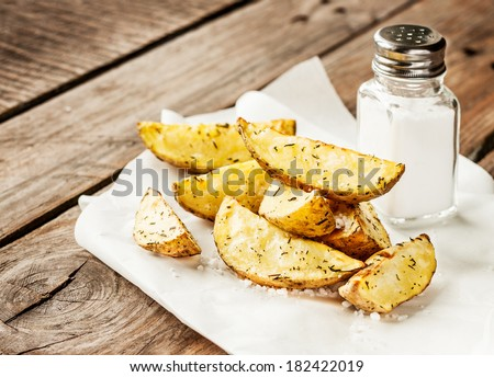 Potato wedges and salt shaker on rustic vintage planked wood table - snack bar or pub menu - stock photo